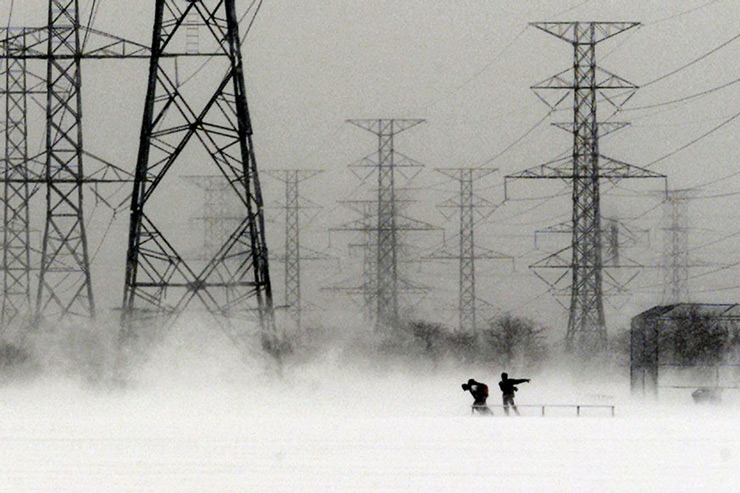 School going students are dwarfed by power towers as they fight their way across an open field during a winter storm in Pickering, Canada.