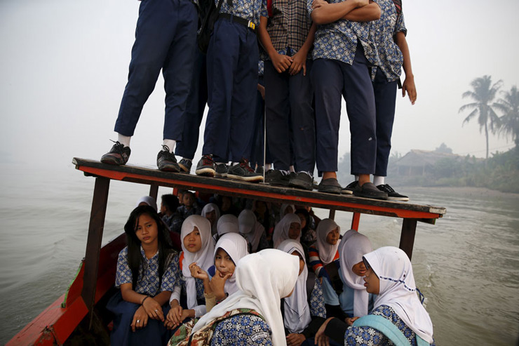 Students stand on the roof of a wooden boat as haze blankets the Musi River while they travel to school in Palembang, on Indonesia