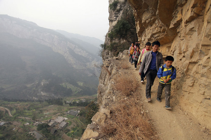 Xu Liangfan escorts students on a cliff path as they make their way to Banpo Primary School in Shengji county, Bijie city in Guizhou province, China.
