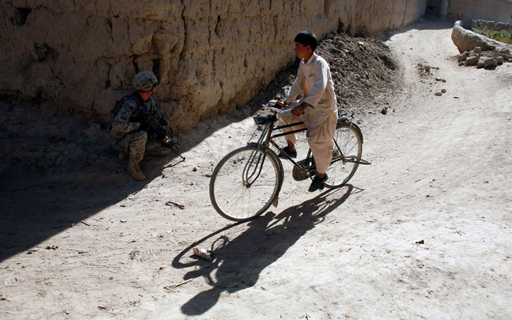 An Afghan schoolboy cycles past a soldier from the US Army