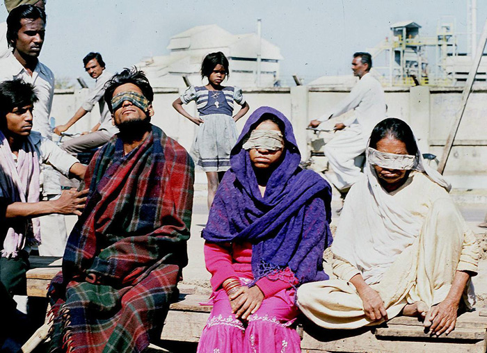 9.A December 1984 photo shows victims who lost sight after a poison gas leak from a pesticide plant in Bhopal, in front of the US Union Carbide factory (shown in background). #