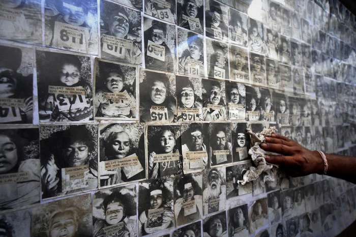 10.A worker cleans dust as he displays a panel of photographs of some of the thousands of people who died in the 1984 Bhopal gas disaster at the forensic department of Gandhi Medical college in Bhopal on June 8, 2010. #