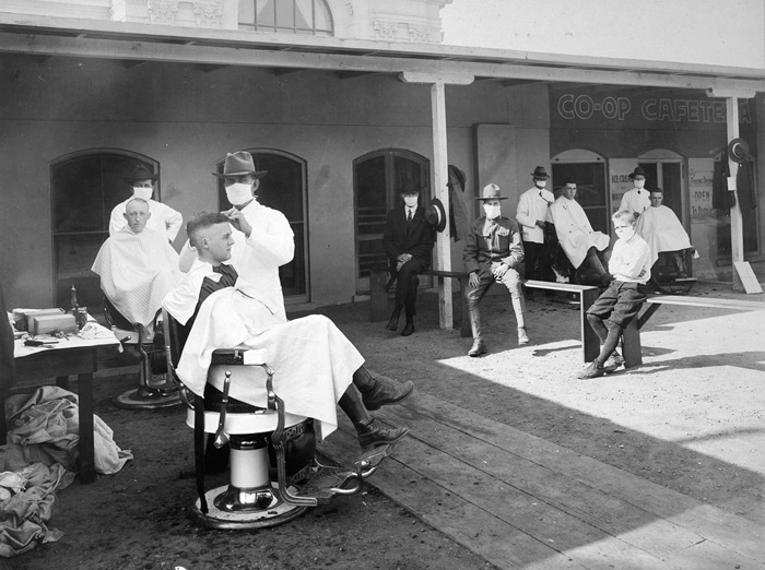 8.An open-air barber shop. Public events were encouraged to be held outdoors to hinder the spread of the disease during the influenza epidemic. Photographed at the University of California, Berkeley, in 1919. #