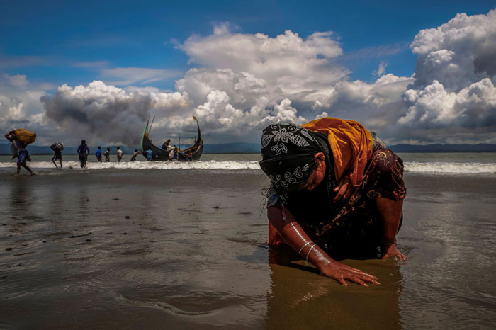 An exhausted Rohingya refugee woman touches the shore after crossing the Bangladesh-Myanmar border by boat through the Bay of Bengal, in Shah Porir Dwip, Bangladesh.
