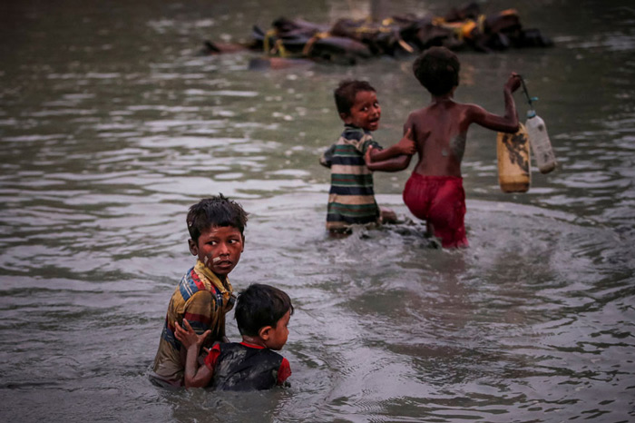 Rohingya siblings fleeing violence hold one another as they cross the Naf River along the Bangladesh-Myanmar border in Palong Khali, near Cox's Bazar, Bangladesh.