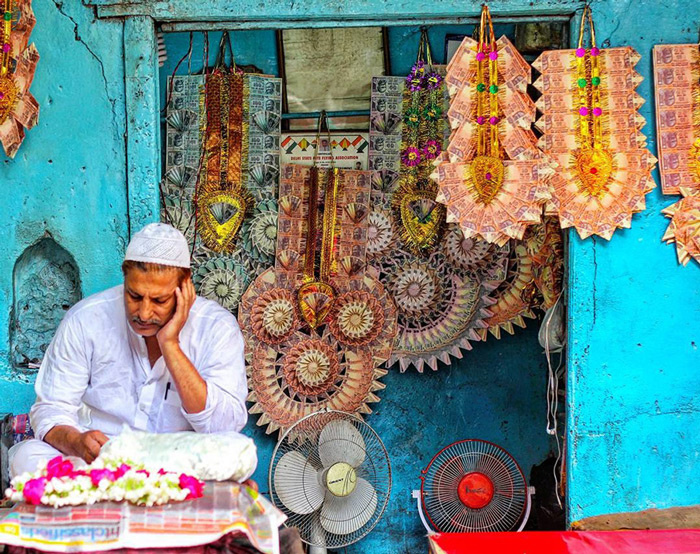 A shopkeeper is seen busy reading a book in Delhi.