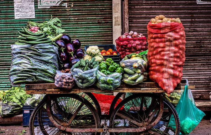 A vegetable vendor is getting ready for work.