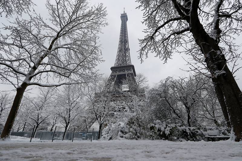 At the Eiffel Tower, snow has turned into ice on platforms and stairs, making it difficult for tourists to move about