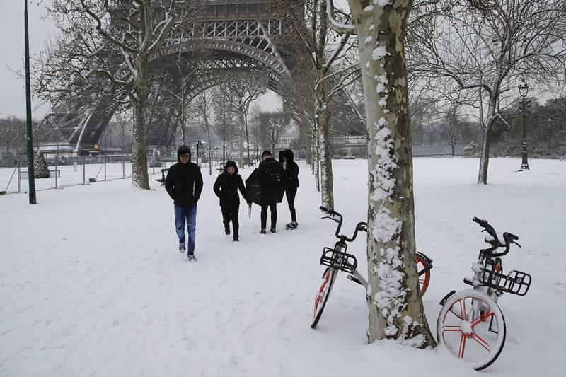 People stroll on the snow-covered Champ de Mars during a snowfall in Paris, France. The Eiffel Tower is closed