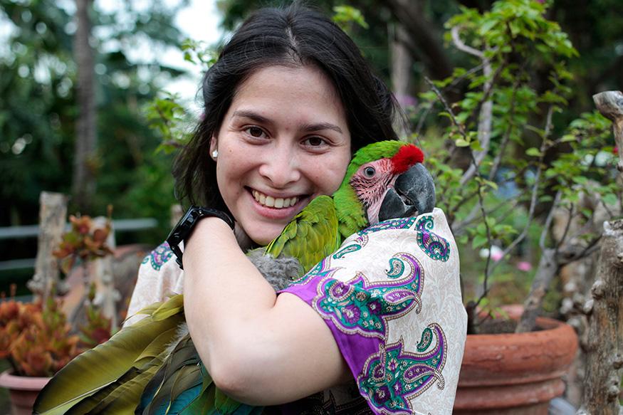 Hazel Quant hugs her pet, a giant parrot, named