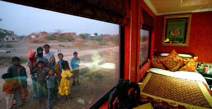 Villagers react to the camera from outside the luxury train, Palace on Wheels (POW), on the outskirts of the historic town of Jodhpur in the desert Indian state of Rajasthan