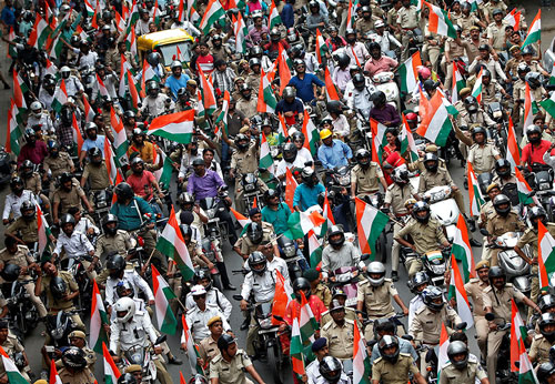 People hold tricolour flags as they participate in a rally on the eve of India