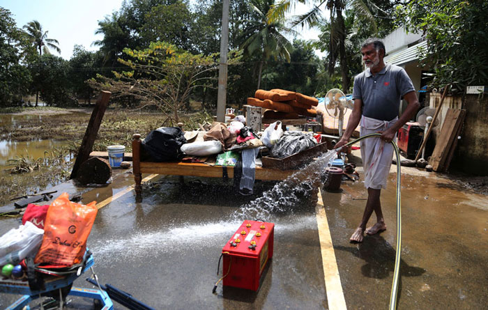 A resident cleans household goods salvaged from sludge in his flood affected house in Kochi