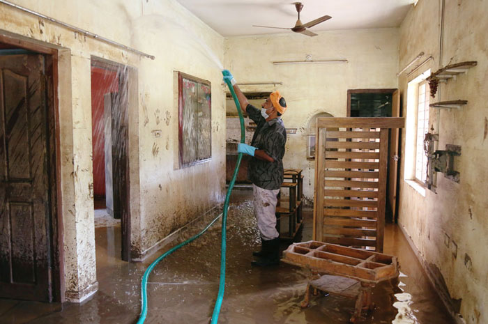A volunteer cleans a house following floods on the outskirts of Kochi in Kerala.