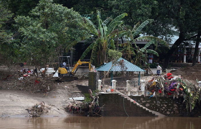 An excavator removes muck caused due to recent floods on the banks of Periyar river, on the outskirts of Kochi in Kerala