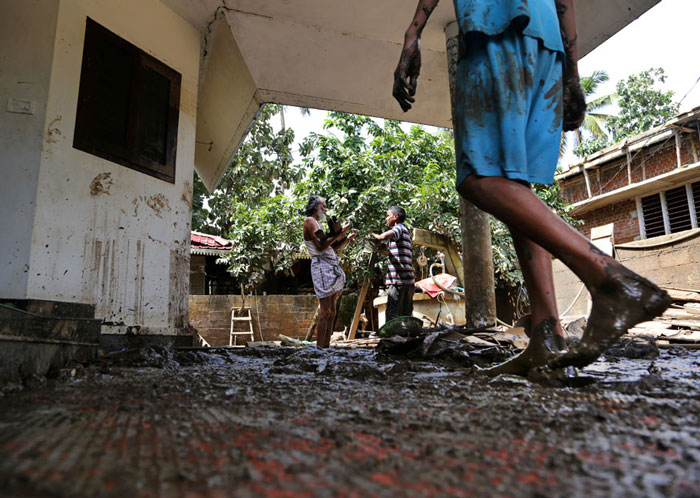 Residents salvage household goods outside their flood affected house in Kochi.