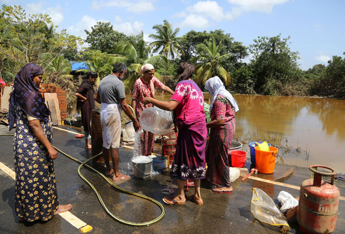 Residents wash household goods after salvaging them from sludge and muck accumulated inside their flood affected houses in Kochi.