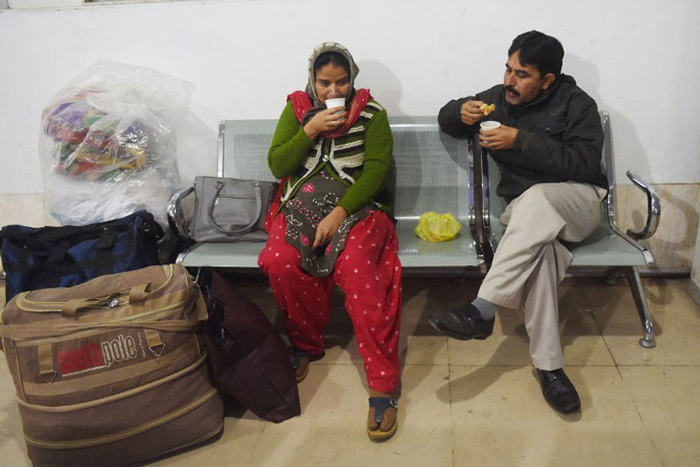Stranded Indian passengers travelling with the Samjhauta Express, also called the Friendship Express that runs between Delhi and Attari in India and Lahore in Pakistan, eat breakfast at the waiting area at Lahore railway station.