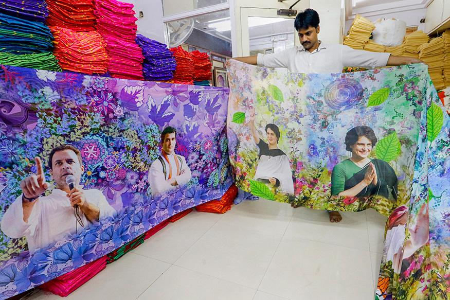 A salesman displays sarees with images of Congress leaders Rahul Gandhi and Priyanka Gandhi Vadra printed on them, ahead of the Lok Sabha polls, at a shop in Surat,