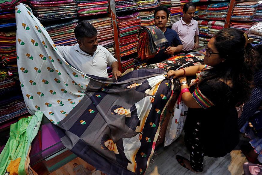 A salesman shows a sari with printed images of Priyanka Gandhi Vadra to a customer inside a shop in Kolkata.