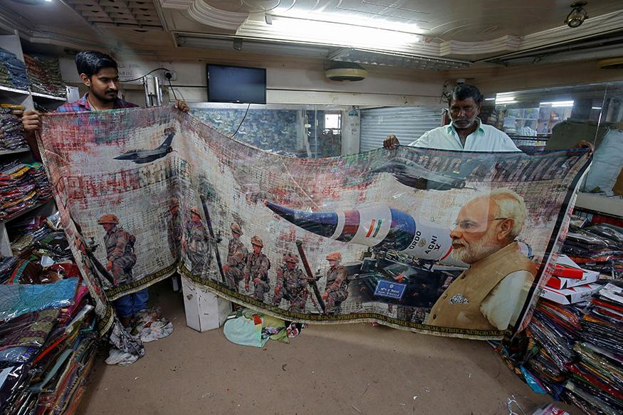 Salesmen pack a sari with printed images of India