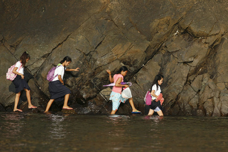 A woman accompanies some students as they wade in the shallow part of a rocky beach to their school to attend the first day of classes in Sitio Kinabuksan, Kawag village, Manila.