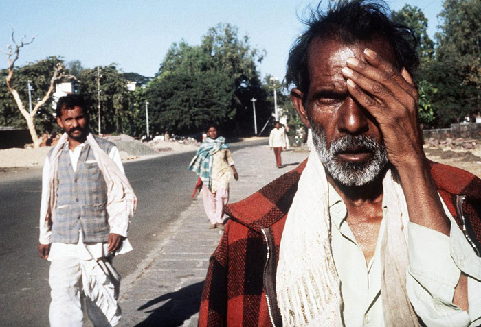 6.A victim of the Bhopal tragedy walks in the streets on December 4, 1984. In the background is the site of the factory. #