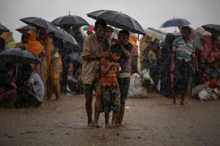 Rohingya refugees try to take shelter from torrential rain as they are held by the Border Guard Bangladesh (BGB) after illegally crossing the border, in Teknaf, Bangladesh.
