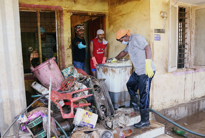 Volunteers clean a house following floods on the outskirts of Kochi in Kerala.