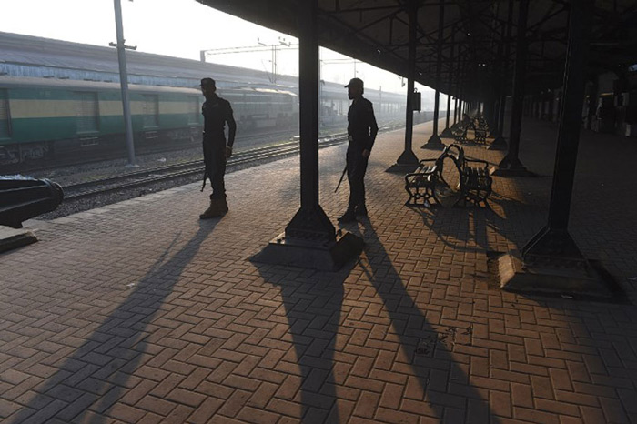 Pakistani policemen stand guard at Lahore railway station, as the authorities suspended train operations temporarily between India and Pakistan.