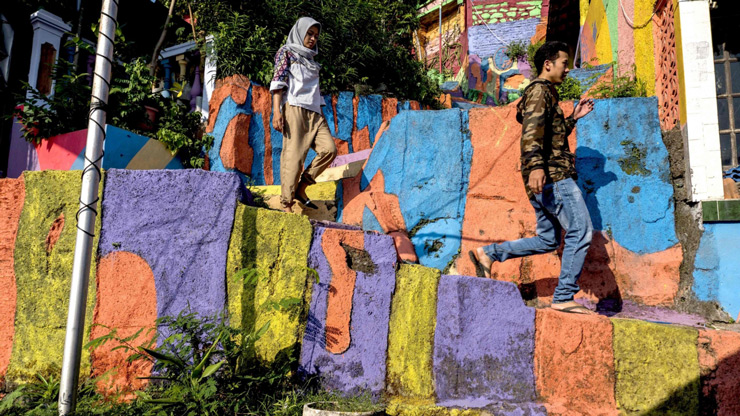 "Villagers walking along a path at an Indonesian hamlet dubbed ""the rainbow village"" in Semarang, central Java."