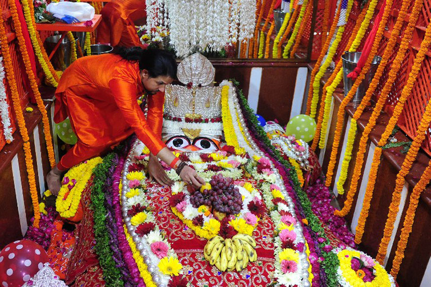 Hindu priest decorates a statue of the Hindu monkey god Hanuman during for Hanuman Jayanti at the Bade Hanuman temple near Sangam in Allahabad.