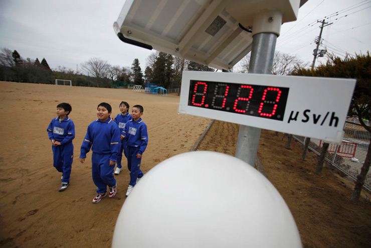 Students walk near a Geiger counter, measuring a radiation level of 0.12 microsievert per hour, at Omika Elementary School, about 13 miles from the tsunami-crippled Fukushima Daiichi nuclear power plant, in Minamisoma, Japan.