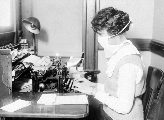 7.A typist wears her influenza mask in October of 1918. Worried by the hold that disease had taken in New York City, practically all workers covered their faces in gauze masks as a protection against disease. #