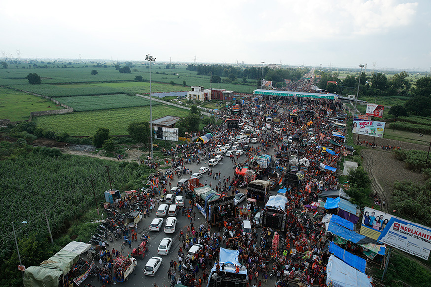 Kanwarias walk past a toll gate on a national highway during a religious pilgrimage near Meerut.
