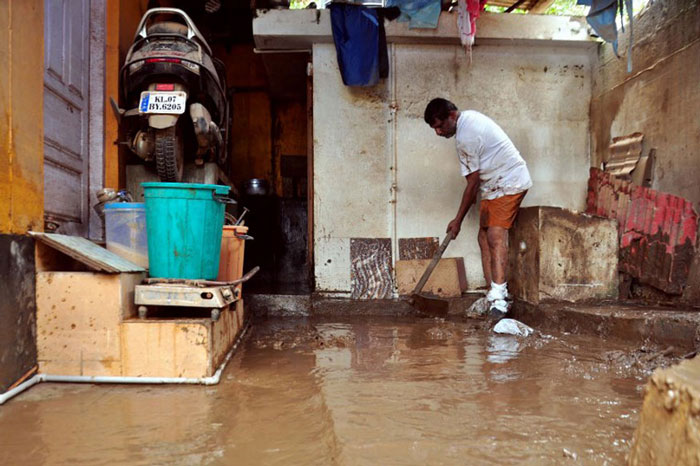 A man cleans the muddy floor of a building in Kochi following widespread flooding in Kerala.